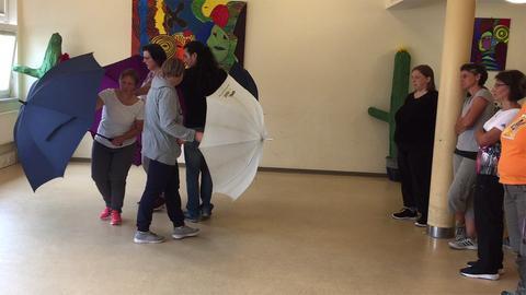 Menschen tanzen mit Regenschirmen