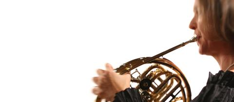 Frau spielt Horn